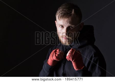 Fighter bearded man wearing tracksuit on black background