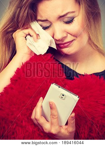 Betrayal bad relationship hurt love concept. Sad heartbroken woman crying and looking at her phone. poster