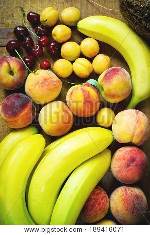 Fresh fruit variation. Ripe bananas, peaches, apricots and cherry on the table, top view