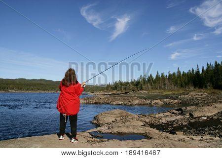 Woman fishing by a lake in rocky landscape
