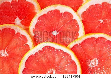 Grapefruit background. Juicy citrus slices as a colorful background