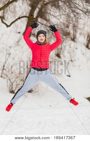 Outdoor sport exercising sporty outfit ideas. Woman wearing warm sportswear training exercising outside during winter jumping out of joy.