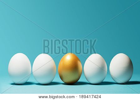 Concept of individuality exclusivity better choice. One golden egg among white eggs on blue background.