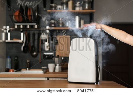 Healthy air. The humidifier distributes steam in the kitchen in loft style. The girl is holding her hand over the steam. Health and safety.