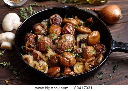 Cooked mushrooms in frying pan on wooden table close up view