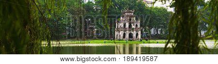 Hanoi, Vietnam. Turtle Tower at Hoan Kiem Lake in Hanoi, Vietnam. Tree at the foreground, cloudy moody weather