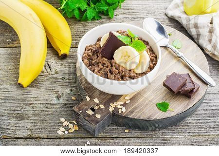 Chocolate oatmeal for breakfast with slices of a ripe banana and pieces of bitter good chocolate in a white ceramic bowl on a wooden background in a horizontal position. Example of a healthy