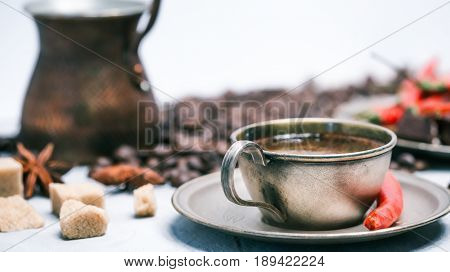 Cup of coffee, copper coffee pot and roasted coffee beans  with sugar and red chili peppers on white background. Selective focus