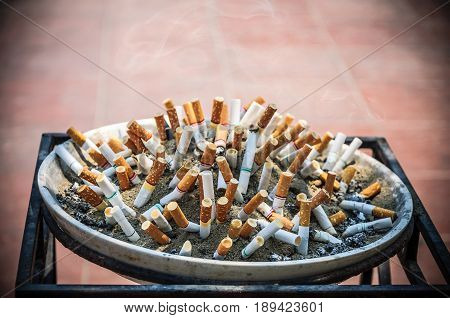 Cigarette butt cigarette on Ashtray with sand and cigarette stubs outdoors