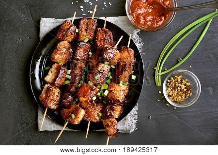 Bbq meat on wooden skewers on plate top view