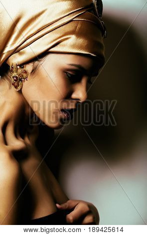 beauty african woman in shawl on head, very elegant look with gold jewelry close up mulatto makeup macro