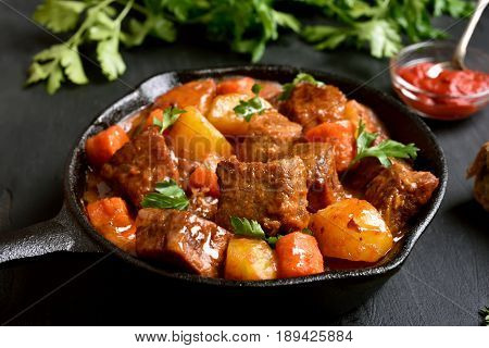 Stewed beef and vegetables in frying pan close up view