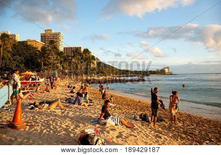 Waikiki, Hawaii - November 30, 2013: Beach goers enjoying sunny weather on famous Waikiki beach