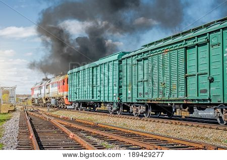 Freight train railroad departure from starion with black smoke