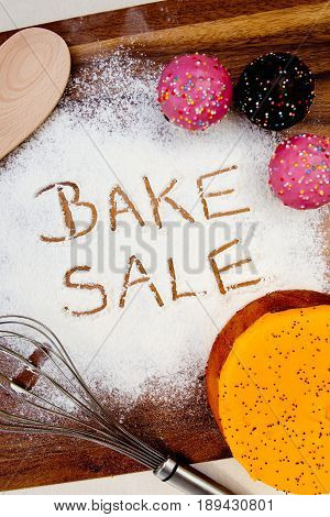 Bake Sale with cake written in flour
