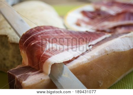 famous Italian dry-cured ham called prosciutto di parma cut by hand