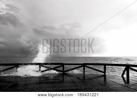 black and white photography of splash of sea on a wooden gangway