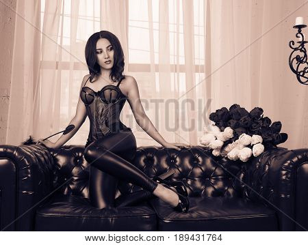Sexy brunette in corset and leather pants. Sensual young woman on a leather sofa. Sepia