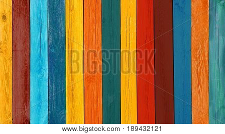 Art Wooden Background. Creative Colorful Wallpaper. Restored old wooden Texture. Wood Surface Fence Panel with boards painted Multicolored Paint Close-up. Wide Horizontal Image with Copy Space