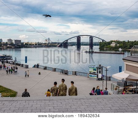 May 25 2017 Kiev Ukraine: three soldiers are walking along Poshtova Square. Kiev cityscape with a view of the Dnieper River.