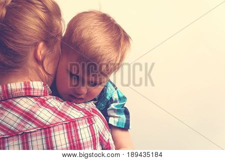 Young mother comforting her little boy. Sad unhappy child hugging his mother. Family relations problems.