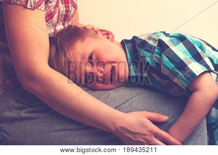 Sad little crying boy hugging his mother at home. Woman comforting her unhappy child. Family relations problems.