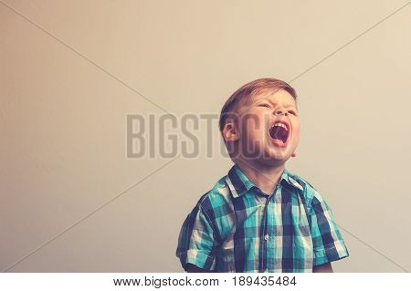 Portrait of angry caucasian child on white background. Little child staying and shouting. Frustration and depression.
