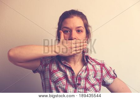 Young Caucasian woman covering her mouth with hands. Stressed or abused woman on white background.