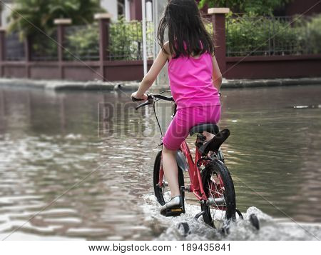 Child Rides a Bicycle Through Flooded Street