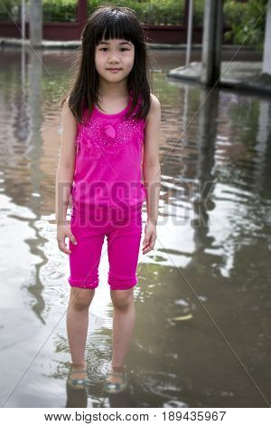 Child Standing in Flooded Dirty Water in the Day