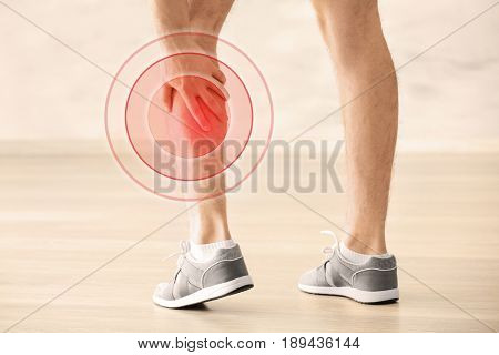 Health care concept. Man suffering from pain in calf, closeup