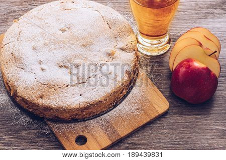Apple pie on a wooden table. Apple pie juice and red Apple.