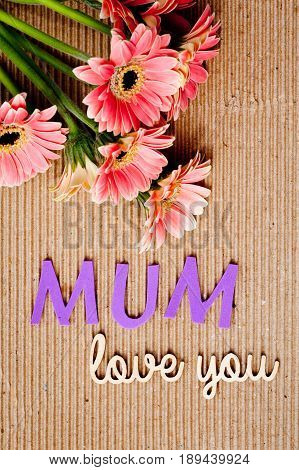 Mother's Day message with flowers on corrugated cardboard background - Mum