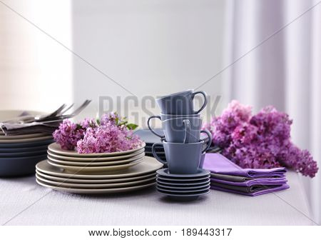 Pile of dishware and lilac blossom on table