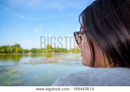 Side face of a woman wearing eyeglasses sitting relax and looking at a natural landscape near the swamp with lotus happily