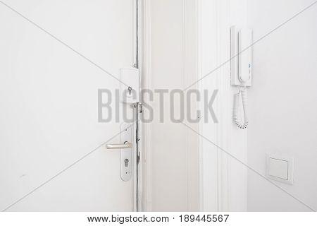 Door Handle , Bar Lock And Interphone System On White Apartment Door