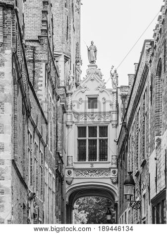 Bridge crossing between buildings over narrow Blinde-Ezelstraat, aka Blind donkey street, near Burg square, Bruges, Belgium. Black and white image.