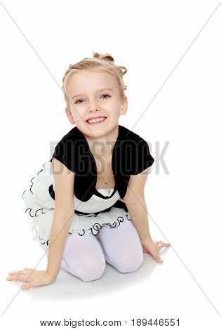 Beautiful little blonde girl dressed in a white short dress with black sleeves and a black belt.The girl kneeling on the floor smiling directly into the camera.Isolated on white background.