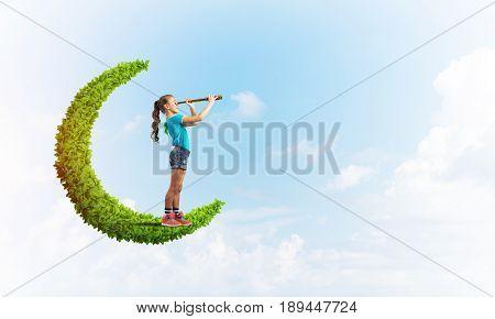 Cute kid girl on green moon in day sky looking in spyglass