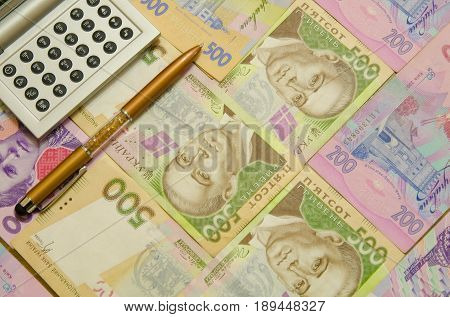A pen and a calculator keyboard against the background of Ukrainian hryvnia banknotes.