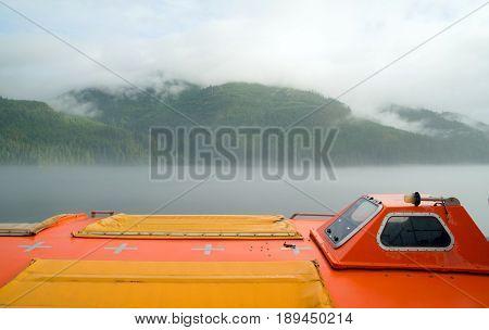 A sealed orange liefboat survival vessel is mounted on a larger ship