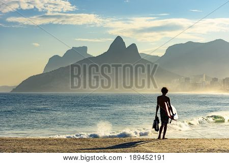 Young bodyboarder looking at the sea and Ipanema beach during a sunny afternoon
