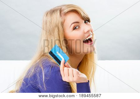 Happy smiling woman holding credit card in hand concept of cashless paying for shopping