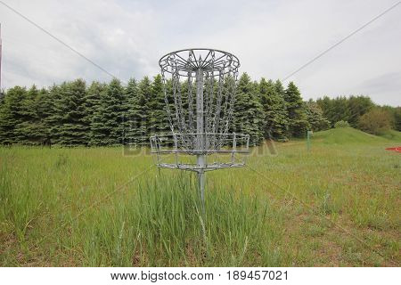 Disc golf basket outside in a field with pine tress