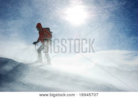 A lonely backcountry skier reaching the summit of the mountain during a snowstorm, horizontal orientation