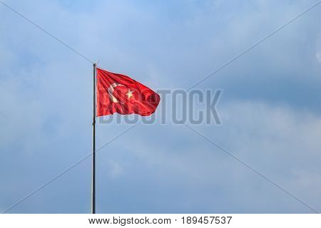 Turkish flag with blue sky with clouds
