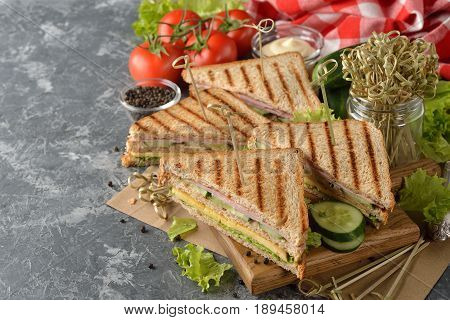 Sandwich with cucumber cheese and ham on a gray background