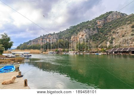 Dalyan canal and boats in the canal with rock graves of ancient greek kings