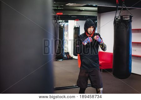 Professional Muay Thai fighter. Male boxer in training sportswear an exercise in sports hall fight with a shadow Strike testing