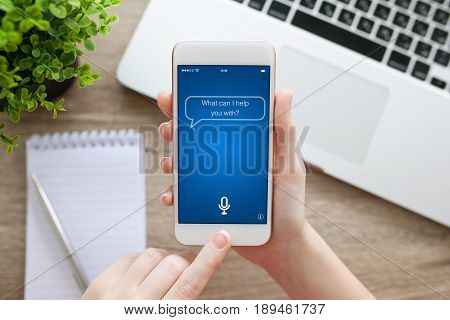 female hand holding white phone with app personal assistant on screen